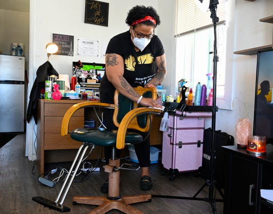 Carmelle Harris uses a sanitizing wipe on her barber chair after cutting the hair of a client.