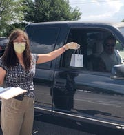 "Outside the Zales store in Allen, Texas, a team member wears a mask and gloves during a ""Curbside Concierge"" appointment."