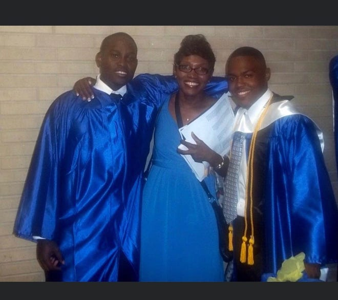 From left Ahmaud Arbery, his mother Wanda Cooper-Jones and his best friend Akeem Baker pose at their high school graduation.