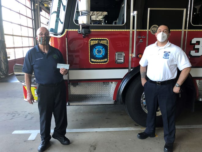 Mount Laurel Mayor Irwin Edelson, left, presents his monthly township pay to Fire Chief John Colucci to benefit the local  firefighters foundation. He and two other council members are donating their pay to first responders while the coronavirus health emergency is in effect.