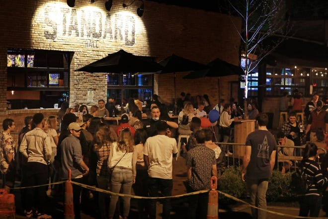 """In spite of COVID-19 crowd limitations, a crowd gathers to drink at Standard Hall, a bar in Columbus' Short North Art District on Friday, May 15, 2020 about 11 pm. The bar's owners, Corso Ventures, told WBNS television, """"Standard Hall has exactly 45 tables on the patio, spaced 6 feet apart. Based on the guidelines set forth by the state, we are not allowing parties of more than 10 at each table."""""""
