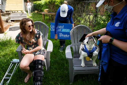 Joely Lomas of Whales pets Griff as Betsy McKibbin puts a sign in their yard and Erin Bell adjusts his cap for a photo on Saturday, May 16, 2020, in Des Moines. Griff was visiting some local graduates because Drake canceled the in-person commencement ceremony because of COVID-19 and is holding it online instead.