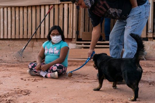 April 20, 2020 Annabelle Dinehdeal, 8, watches as he father Eugene Dinehdeal, plays ball with their dog Wally on family compound in Tuba City, Ariz., on the Navajo reservation.