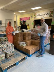 Members of the Dawoodi Bohra community helping to pack food with Todd Lipa of CARES of Farmington Hills.
