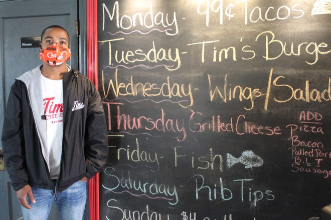 Tim Freeman, owner of TIm's Bar and Grill in Fremont, stands next to his daily special board. Freeman and other Ohio restaurant owners will be able to offer inside-dining service starting Thursday.