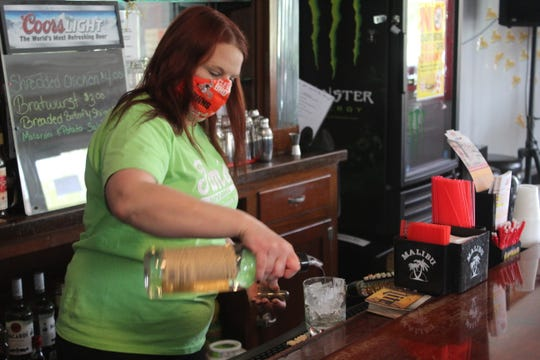 Deanna Welch, an employee at Tim's Bar and Grill in Fremont, pours a drink for a customer seated outside at the restaurant's patio area Saturday.