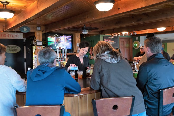 Angie Mortier pours a drink for a customer at Irish Greens Golf Course on Friday, May 15.  The business was one of man taverns and restaurants to start hosting patrons after the Wisconsin Supreme Court struck down on Wednesday the state's second Safer at Home order, set to expire on May 26,