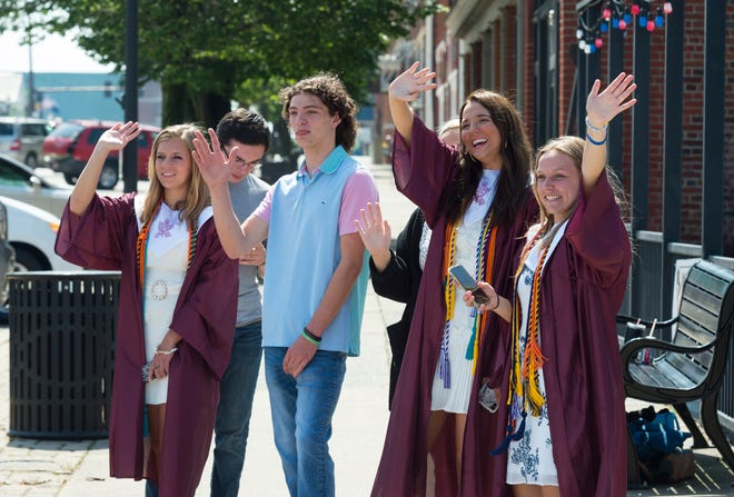 Graduates wave to their friends during the Blue Unit graduation parade for the Henderson County High School Class of 2020 at HCHS Saturday morning, May 16, 2020.