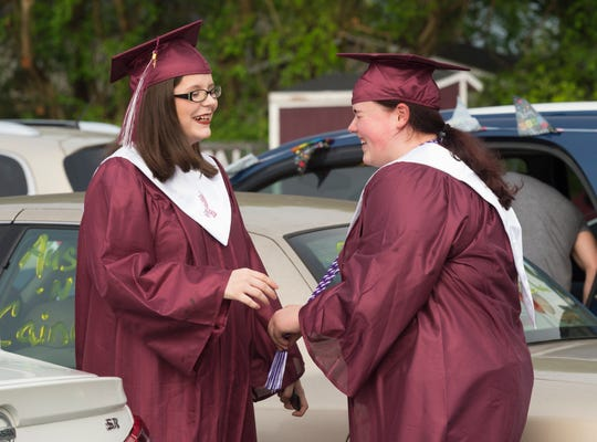 Megan Stull, left, and Diana Williamson, right, laugh before a drive-thru ceremony and graduation parade for the Henderson County High School Class of 2020 at HCHS Saturday morning, May 16, 2020.