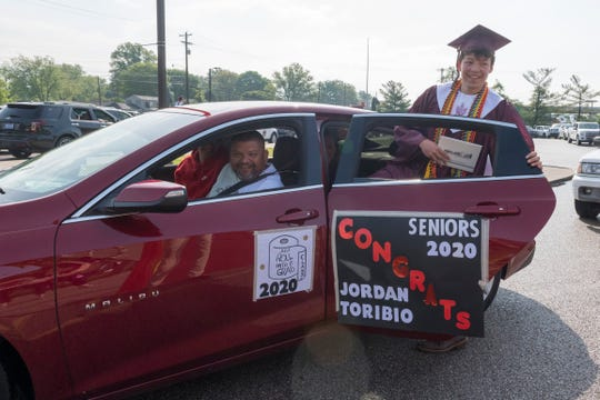 Jordan Toribio climbs back into a car after receiving his diploma cover during a drive-thru ceremony and graduation parade for the Henderson County High School Class of 2020 Saturday morning, May 16, 2020.