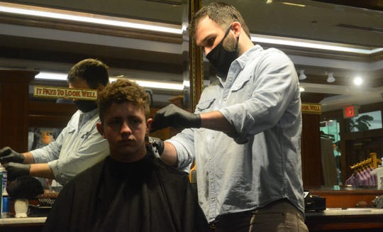Chase Hudson of Brandon gets a long overdue trim from barber Blake Stevens at the Great Scott clothing and barber shop in Jackson on the day restrictions were eased for businesses across the city on Saturday, May 16, 2020.