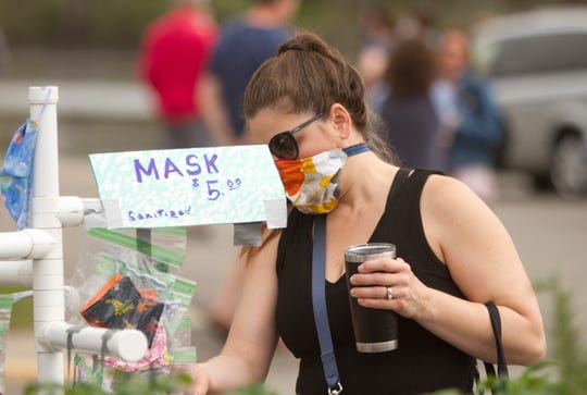 Brighton resident Emily Martina shops for masks offered by Gedeon Farms for her two daughters at Brighton's farmers market Saturday, May 16, 2020.
