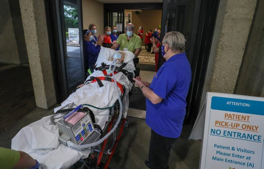 Paula Eaton is taken by gurney from Baptist Health Louisville on Saturday, May 16, 2020, to a waiting ambulance to be transported to Kindred Health. Eaton was in the Baptist Health ICU for 51 days, making her the patient who has been in the Baptist Health Louisville ICU the longest of any COVID-19 patient. Her husband, Jim, was waiting for her with extended family on hand. Nurses lined the hallway as she exited. Paula and Jim have been married for 52 years.