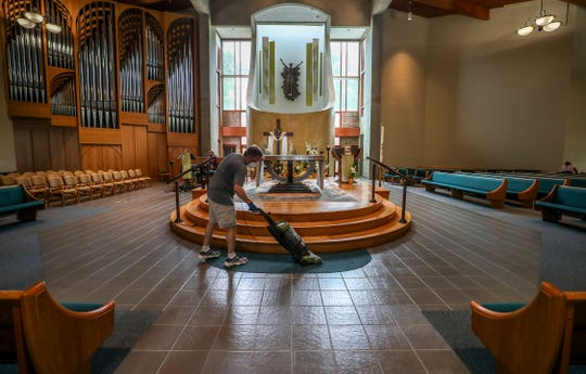 """Greg Nopper vacuums around the altar at St. Margaret Mary Catholic Church.  On Saturday, May 16, 2020, parishioners at the church gave the church a deep cleaning in anticipation of opening back for services on Wednesday. Many steps are being taken to ensure safety, including changes to communion, closing half of the pews, closing the """"cry room"""" and even removing the small pencils from the backs of the pews."""