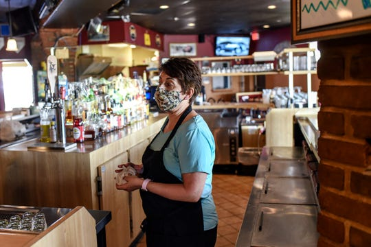 Owner Harea Bates works near the bar at Harry's Place on Friday, May 15, 2020, in Lansing.