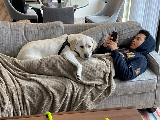 Mel Tucker's dog, Prince Jaxson, lays with his son, Christian, as the family of the new Michigan State football coach adjusts to life during the coronavirus.