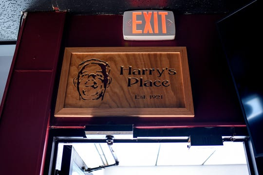 A sign using the image of the original owner Harry Andros hangs over the door at Harry's Place on Friday, May 15, 2020, in Lansing.