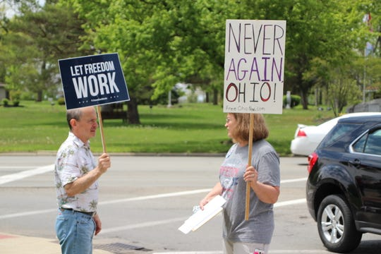 Free Ohio Now rally participants Steve and Mary Stoneburner hold up signs during the event on Saturday at the Harding Memorial on Delaware Avenue in Marion. The next rally is tentatively set for Memorial Day, according to Mary Stoneburner.