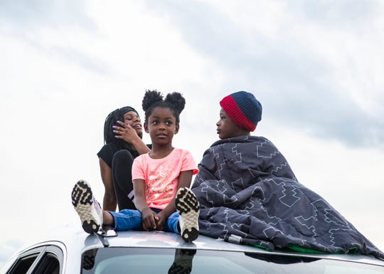Siblings K'leigh Hudson and Rickey Hunt sit on top of a truck before a movie starts at the Malco Summer Drive-In in Memphis, Tenn., on Friday, May 15, 2020. The drive-in becomes the first movie theater to reopen during the pandemic.