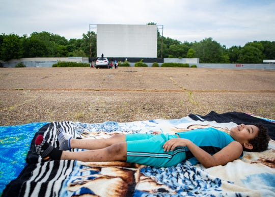 Lamarcus Blades stretches out on his blanket before a movie starts at the Malco Summer Drive-In in Memphis, Tenn., on Friday, May 15, 2020. The drive-in becomes the first movie theater to reopen during the pandemic.