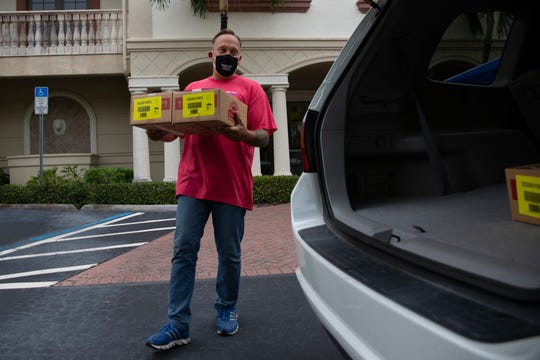 Jason Buro loads supplies Into a car during a drive-thru food pantry event Saturday, May 16, 2020, in Naples