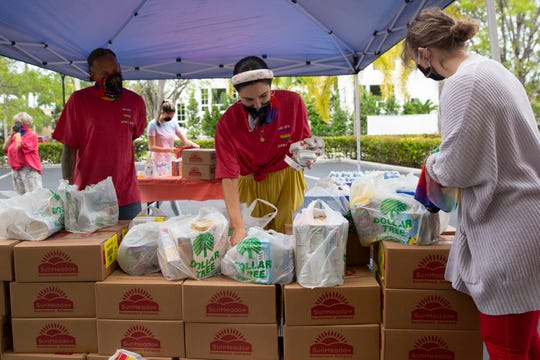 Naples Pride members Callhan Soldavini, center, organizes donated goods for her organization's food pantry event, Saturday, May 16, 2020, in Naples