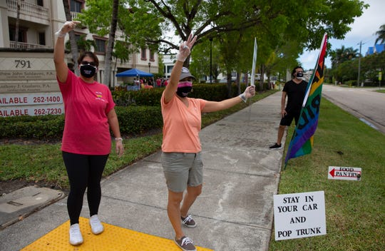 Naples Pride members Yaisel Aguilar, let, Sandy Fernan and Antonio Concha welcome residents to their organization's food pantry event, Saturday, May 16, 2020, in Naples