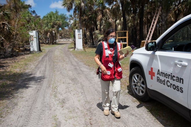 Red Cross volunteer Dora Koop assesses the fire damage to Lisa Cook and Carl Radzik home, Saturday, May 16, 2020, in Golden Gate Estates.