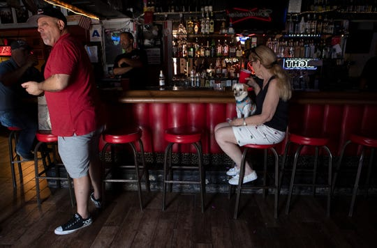 Red Barn owner John Labrano, left, stands as Ruth Ann Barshop of Indian Wells sits inside the bar in Palm Desert, Calif., on Saturday, May 16, 2020. The bar has been closed since mid-March when Gov. Newsom issued the state's stay-at-home order to slow the spread of COVID-19.