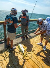 Roger Negre, center, shows off his crevalle jack at the Navarre Beach Fishing Pier on Saturday, May 16, 2020. Crews have finished a $1.2 million project to install new, weather-resistant wooden planks down the length of the pier.