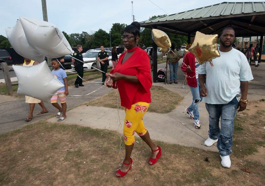 Donna Jones and her son, DeVarrian Virgin, prepare to release balloons to honor the memory of Marcus Virgin on Friday at Westernmark Park.