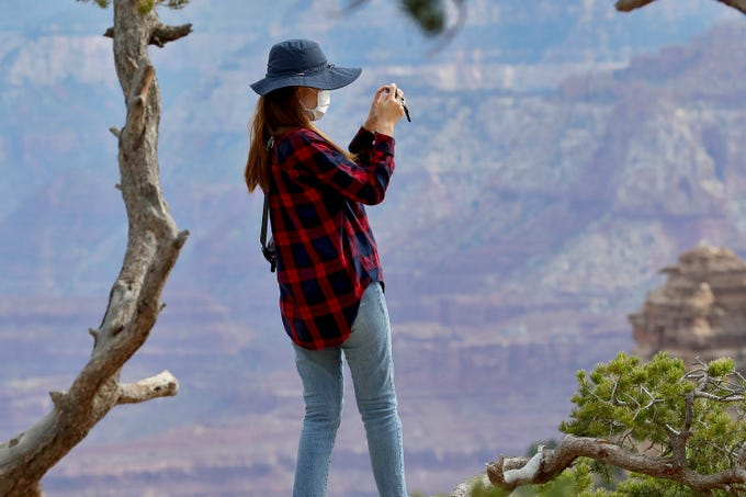 A visitor takes a photo at the Grand Canyon Friday, May 15, 2020, in Grand Canyon, Ariz. Tourists are once again roaming portions of  Grand Canyon National Park when it partially reopened Friday morning, despite objections that the action could exacerbate the coronavirus pandemic.