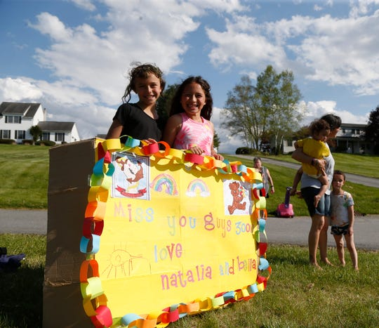From left Natalia Pavon and Bella Martinez, students at Beekman Elementary School stand behind the billboard they made for the school's parade on May 15, 2020.