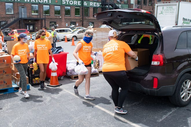 Volunteers load cars with an assortment of foods during the York County Food Bank's Pop-Up Drive-Thru Food Distribution at the John Wright Restaurant Saturday, May 16, 2020.