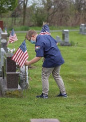 Max Fraser places a flag at a veteran's grave at Holy Angels Cemetery in Scottsville on Saturday, May 16, 2020.