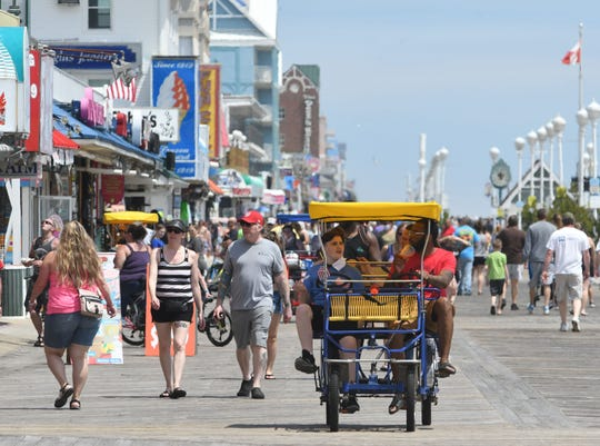 John Phillips, 12, and Paul Goodin, of York, peddle a bike down the boardwalk as thousands flocked to Ocean City, Md., on Saturday after the mayor opened the hotels, beach and boardwalk for visitors after being closed for weeks. Beaches in New Jersey, Delaware and Maryland are slowly reopening during the coronavirus pandemic.