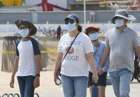 Some chose to wear facemasks as thousands flocked to Ocean City on Saturday, May 16, after the mayor opened the hotels, beach and Boardwalk for visitors after being closed for weeks.