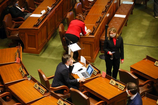 Minnesota House Speaker Melissa Hortman, standing, right, confers with Majority Leader Ryan Winkler, left, as the House met to take up several bills, including the insulin affordability bill, Tuesday, April 14, 2020 in St. Paul.