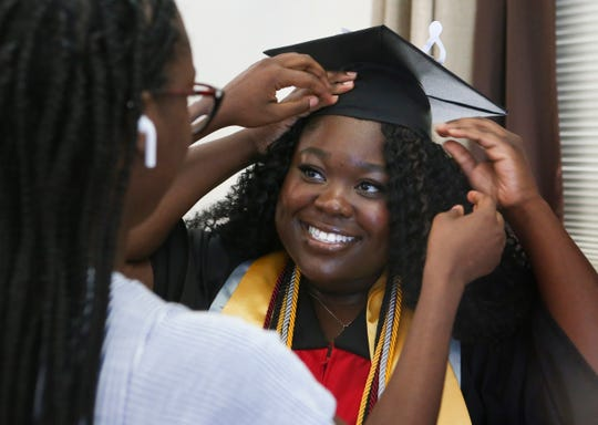 Nursing student Ifeoluwa Fisher get a hand with her mortarboard and gown from her sister Ayo as she takes part in the Delaware State University remote-commencement with her family at their home in Townsend Saturday.