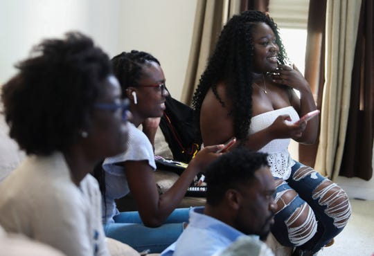 Nursing student Ifeoluwa Fisher (right) watches the early stages of her Delaware State University remote-commencement with her family before pulling on her cap and gown at their home in Townsend Saturday.