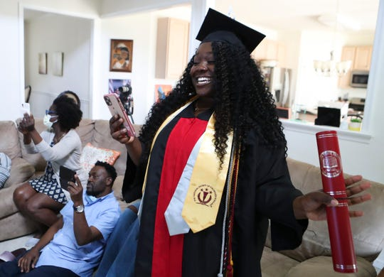 Nursing student Ifeoluwa Fisher celebrates during the Delaware State University remote-commencement with her family at their home in Townsend Saturday.