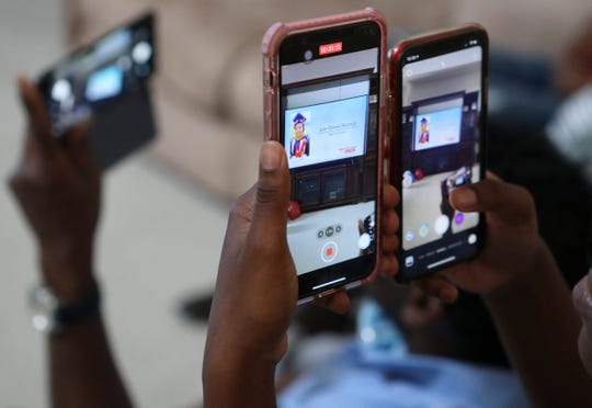 Family members turn their cellphone cameras on their television as nursing student Ifeoluwa Fisher takes part in the Delaware State University remote-commencement at her family home in Townsend Saturday.