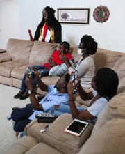 Nursing student Ifeoluwa Fisher waits for her time to stride across the stage (her living room) as family members join her during the Delaware State University remote-commencement at their home in Townsend Saturday.  Watching are her brother, Andre Jr. (red shirt), her mother Tokunbo, sister Ayo (right) and father Andre Sr. (seated on floor).