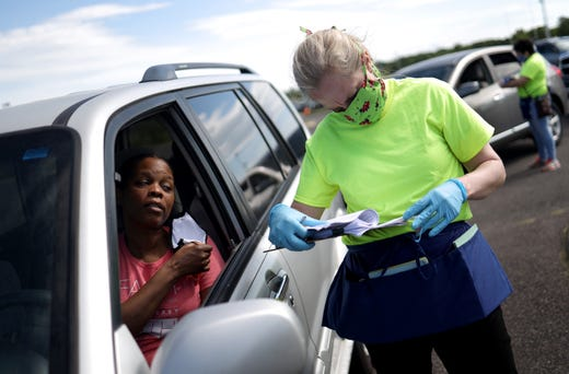 Rep. Abigail Spanberger (D-VA) helps to register families as they wait in line in their vehicles for food to be distributed by the group Empowering Culpeper at the Culpeper Sports Complex May 16, 2020 in Culpeper, Virginia.