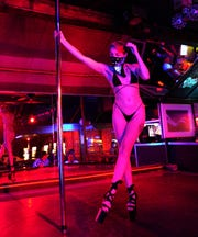 "Cleo, a dancer at The Den strip club in Cheyenne, Wyoming, works the pole while wearing a mask during the club's reopening Friday night. The club hosted a ""masks on, clothes off"" party to celebrate."