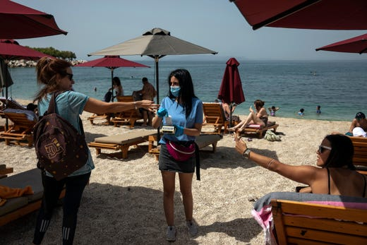 Swimmers pay for sunbeds with an employee of a beach bar who wears a protective mask against coronavirus, at Alimos beach, near Athens, on Saturday, May 16, 2020.