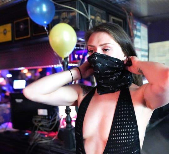 "Boston, a dancer at The Den strip club in Cheyenne, Wyoming, tries on a new mask during the club's reopening Friday night. The club hosted a ""masks on, clothes off"" party to celebrate."