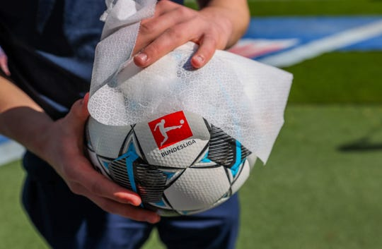 The ball is disinfected after the German first division Bundesliga football match between RB Leipzig and SC Freiburg on May 16.