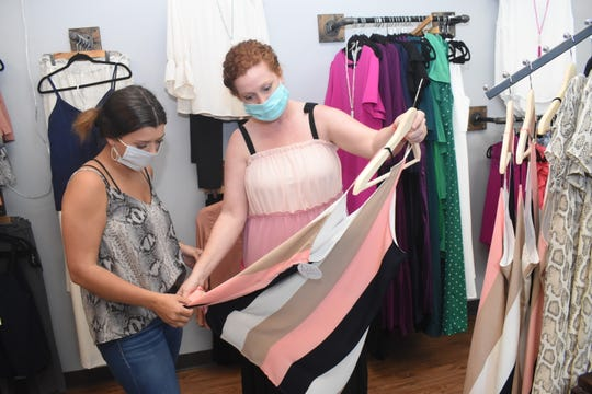 "Hannah Steimel (left) and Brandy Watkins Wills, owner of Addie's Boutique, look over items at the women's dress shop. When Gov. John Bel Edwards issued the stay-at-home mandate, the boutique's sales dropped by 70 percent. ""I had an online platform before all of this started,"" said Wills. ""So it was really focusing more on doing live, doing a lot of video on social media and really pushing my Website www.shopaddiesboutique.com."""