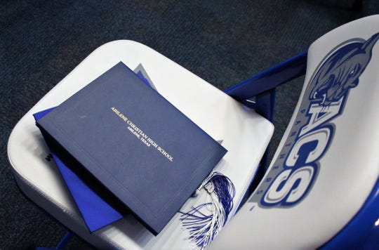 A diploma case rests atop a mortar board, left on a student chair while photos were taken after the ceremony.
